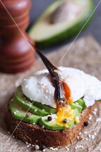 An open sandwich with avocado, poached egg and an anchovy
