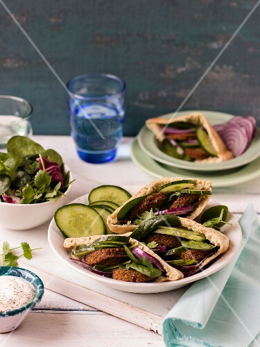 Falafel in pita bread with cucumbers, red onion, spinach and coriander