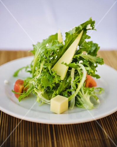 A mixed leaf salad with cheese and tomato