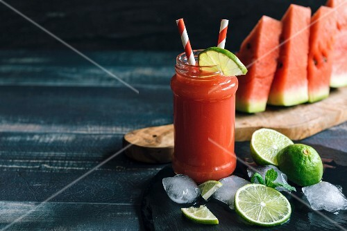 Watermelon juice in a glass with limes