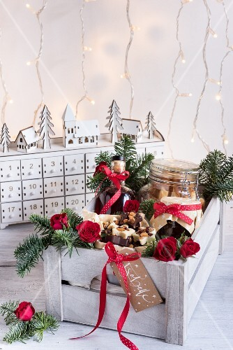 Various Christmas gift foods in a wooden crate
