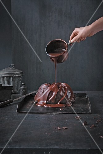 Drizzling chocolate over a chocolate gugelhupf