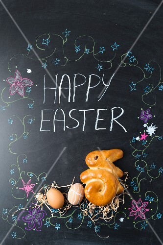 Easter eggs and a bunny (shaped yeast bread) on a chalkboard