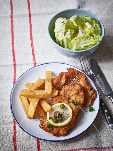 Sausage schnitzel with homemade French fries and lettuce