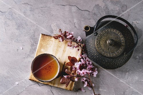 An Asian teapot, a cup and cherry blossom