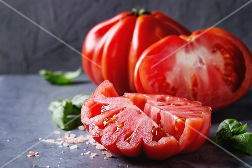 Whole and sliced organic tomatoes Coeur De Boeuf with pink salt and basil on blue gray metal texture background