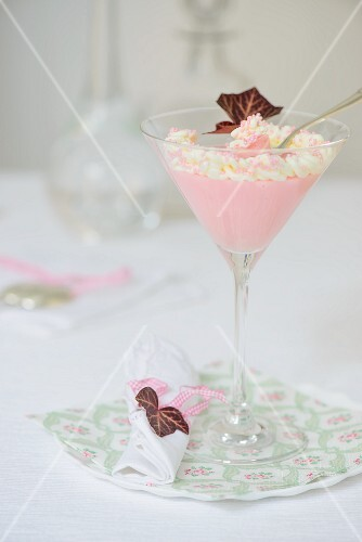 Pink crème dessert with whipped cream in a cocktail glass