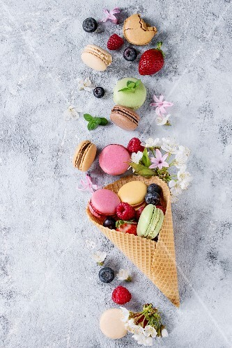 Variety of colorful french sweet dessert macarons with different fillings served in waffle cone with mint and fresh berries