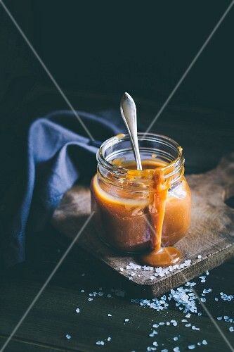 Salted caramel sauce in a glass with a spoon