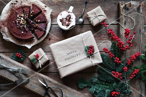 Schokoladenkuchen mit Kakao daneben Weihnachtsgeschenkpäckchen
