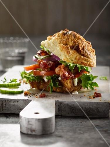 A bacon, tomato, onion and lettuce sandwich