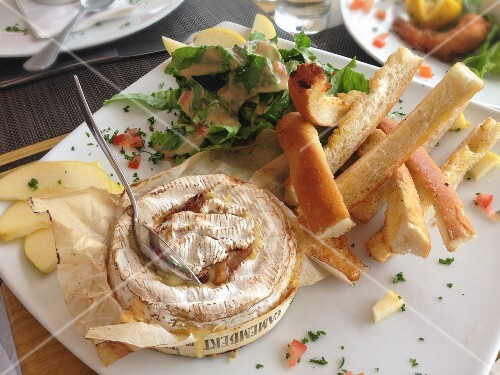 A small wheel of roast Camembert Cheese with toasted bread, apple slices and salad