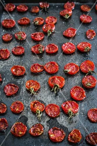 Roasted tomatoes on a black baking sheet