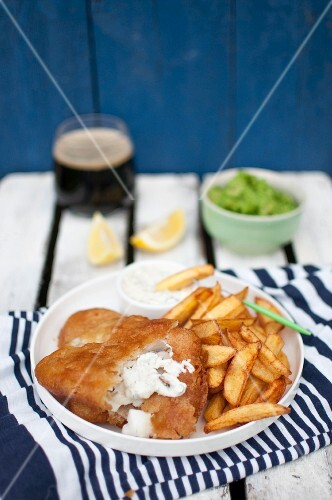 Fish and chips, served with mashed green peas, pieces of lemon tartare sauce and dark beer