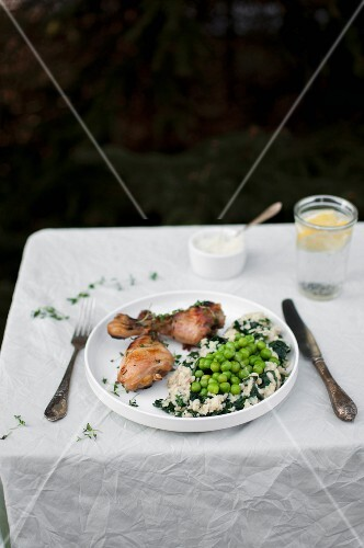 Roasted chicken legs served with millet and green peas