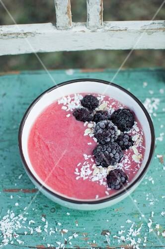 Pink smoothie bowl with strawberries, banana, orange juice and kiwi