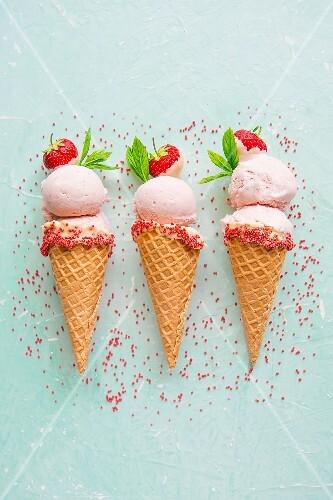 Strawberry ice cream in ice cream cones with sprinkles