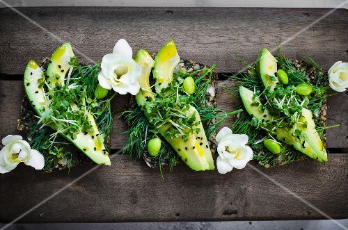 Fresh slices of avaocado on seeded bread with avaocado oil, endemame beans and micro greens