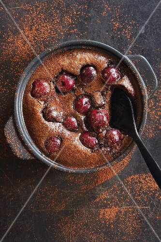 Chocolate and cherry clafoutis, dusted with cocoa powder (top view)