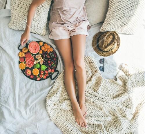 Junge Frau in Shorts relaxed mit Tablett voller frischer Früchte auf Bett (Aufsicht)