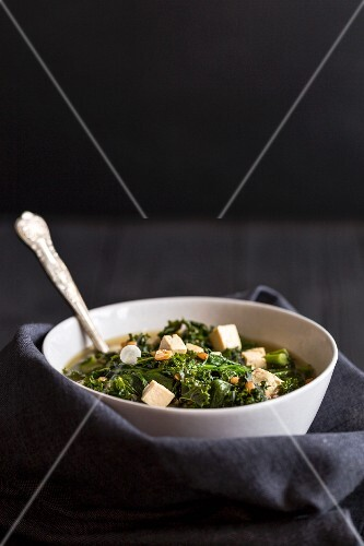 A white bowl filled with vegetarian wholegrain spelt miso soup with tofu, spinach and kale on a black wooden background