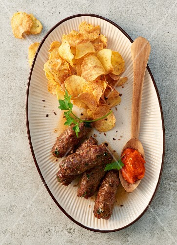 Cevapcici with potato chips and Ajvar (top view)