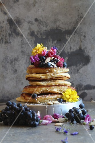Stacked pancakes with fresh berries and flowers