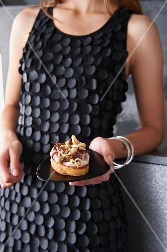 Crostini vom Wurzelbrot mit rotem Bohnenpüree, Zitronen-Calamaretti und krossem Parmaschinken