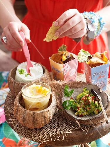 Mango-Mayonnaise, Avocado-Dip, Sauerrahm-Dip und Gemüsechips für eine Party