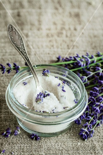 White sugar in glass jars flavored with lavender flowers, standing with tea spoon on table with sackcloth