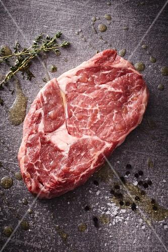 A raw rib-eye steak with thyme, salt and pepper