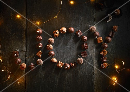 The word 'JOY' made up of chocolate pralines and fairy lights