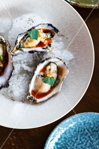 Fresh oysters in sauce on crushed ice