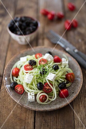 Cucumber spaghetti with feta cheese, olives and tomatoes