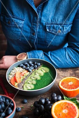 A smoothie bowl with kiwi, orange, blueberries, chia seeds and porridge oats