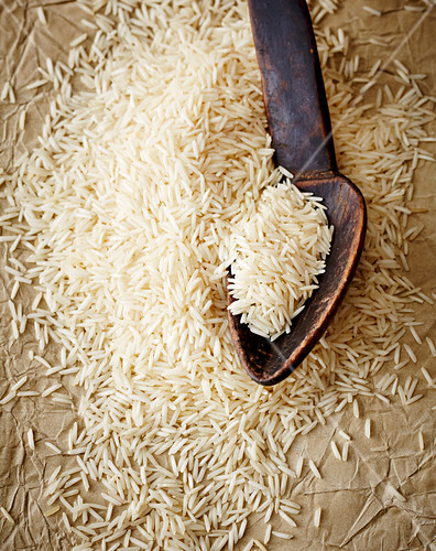 Uncooked rice with a wooden spoon