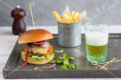 A cheeseburger with chips and beer