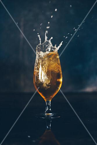 Bier spritzt aus dem Glas