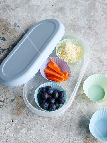 Cheese, carrot sticks and blueberries in silicone cases in a lunchbox