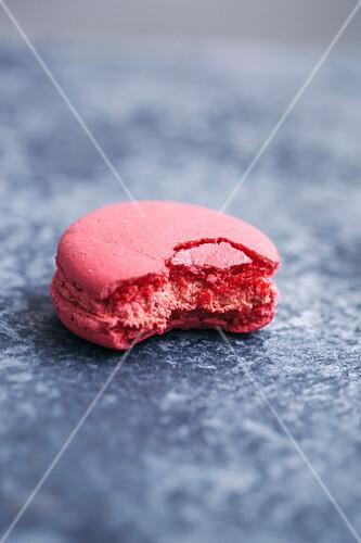 Half eaten pink macaron on grey background