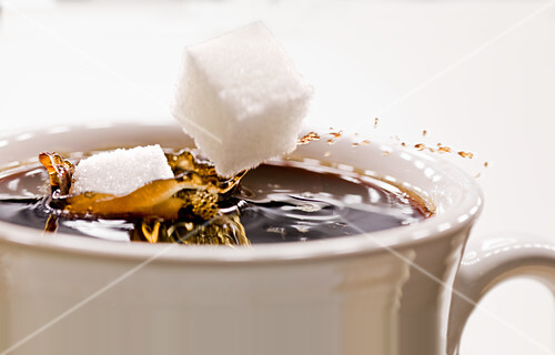 Sugar lumps falling into a cup of coffee