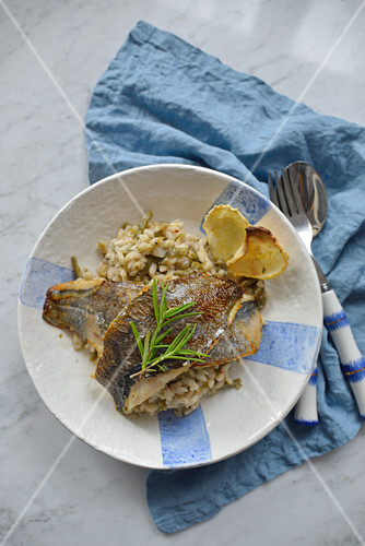 Fried fish fillets on risotto with green beans