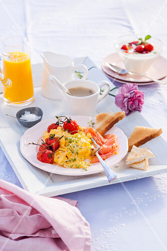 Scrambled egg with cress, smoked salmon and cherry tomatoes for breakfast