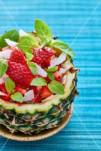 Obstsalat mit Erdbeeren serviert in augehöhlter Ananas