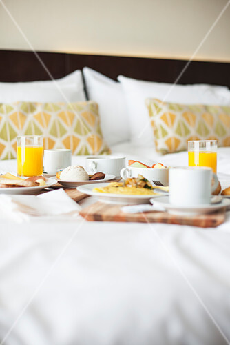 A breakfast tray on a bed in a hotel