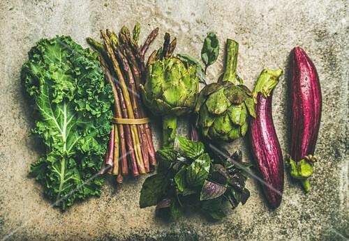 Green and purple fresh vegetables: Eggplans, green beans, kale, asparagus, artichoke, basil