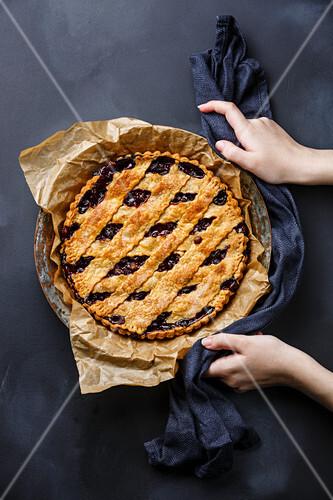 Cherry Pie and female hands on blackboard slate background