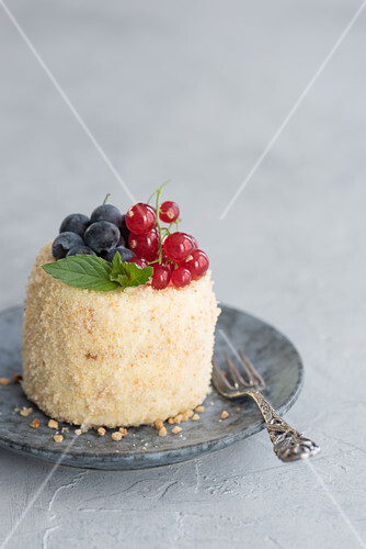 A cream biscuit tart covered with ground almonds and berries