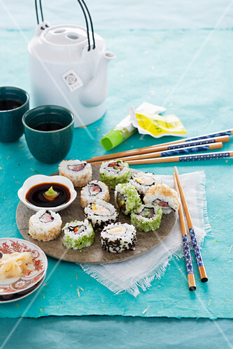 Various inside-out sushi rolls with soy sauce, ginger and wasabi
