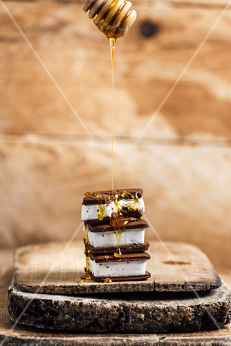 Ice Cream Sandwiches drizzled with honey on a wooden board